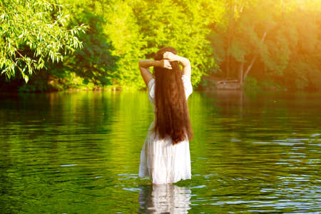 Beautiful brunette girl with very long and thick dark hair standing in the water