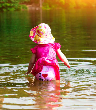 The child bathing in the lake. A little girl in the water. Summer. Sunny day.