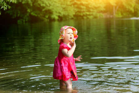 The child bathing in the lake. A little girl in the water. Summer.
