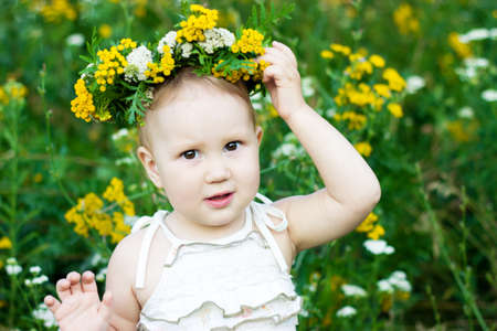 Portrait of a little girl in a wreath from wild flowers. Child closeup. 스톡 콘텐츠