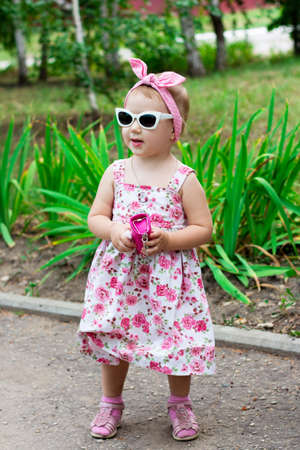 Portrait of a girl child wearing sunglasses, a dress and a handbag. Banque d'images