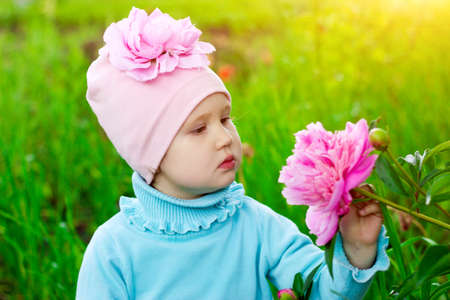The little girl in the garden with peonies flowers. Baby. Child. Close-up