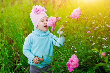 The little girl in the garden with peonies flowers. Banque d'images