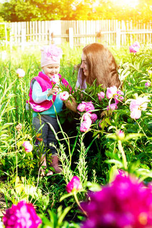 Baby girl with mother in the garden among the flowers. Banque d'images