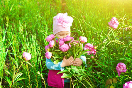 Little girl in garden with a flower bouquet of peonies 스톡 콘텐츠