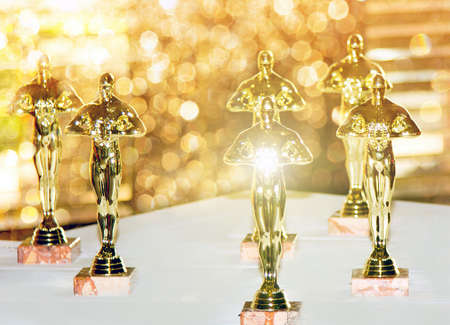 Figurines, award, Oscar. The concept of Victory, games and winnings. Background. Win and Play Stok Fotoğraf