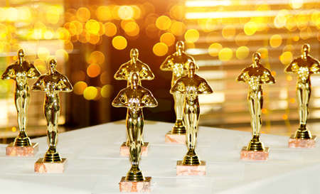 Figurines, award, Oscar. The concept of Victory, games and winnings. Background. Win and Play Archivio Fotografico