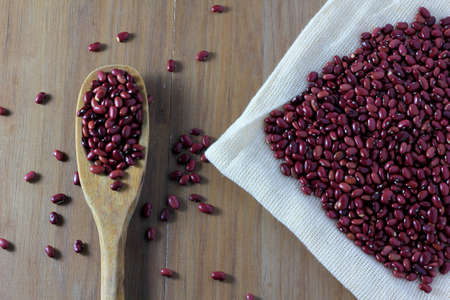 grains red bean bag on side of wooden table, wooden spoon with red beans, top view