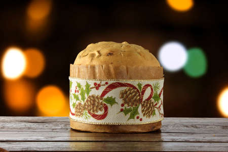 panettone, decorative food, on wooden table, blurred lights in the background, front view Stock Photo