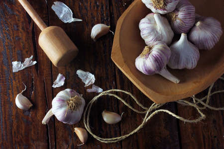 Garlic bulbs inside rustic wooden bowl on rustic wooden table. Closeup of garlic bulbs. Standard-Bild