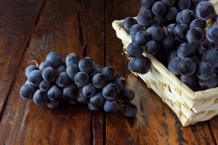 bunches of grapes, inside bamboo fiber basket on wooden table, closeup view 免版税图像