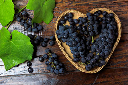 bunches of grape inside basket with heart shape on wooden table, top view