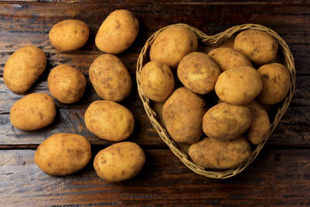 pile of fresh and raw potatoes harvested from plantation and placed in heart shaped wicker basket on wooden table. Top view. Stock fotó