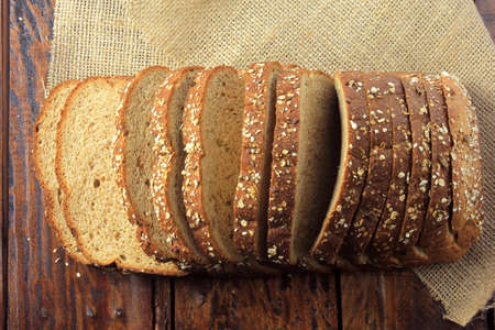 Wholegrain sliced organic bread composed of oats and flax seeds on wooden table. Healthy Diet.Top view