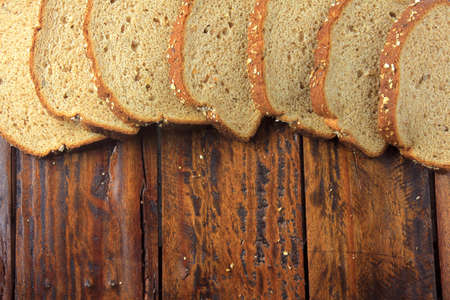 Wholegrain sliced organic bread composed of oats and flax seeds on wooden table. Copy space.Top view