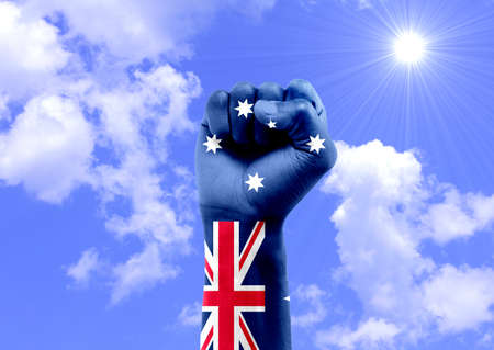 National flag of Australia painted in the hands of people with closed fist celebrating the day of Australia. Front view Imagens