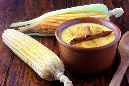 Curau, cream of corn sweet and dessert typical of the Brazilian cuisine, with cinnamon placed in ceramic bowl on wooden table. Copy space. Close-up