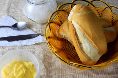 close up french bread on wooden breakfast table with butter and cutlery, top view Фото со стока