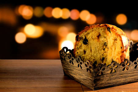 closeup panettone inside box on wooden table, bokeh background with lights, front view Фото со стока