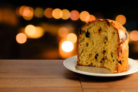 closeup panettone on ceramic plate on wooden table, bokeh background with lights, front view