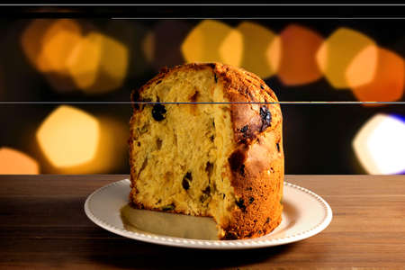 closeup panettone inside ceramic dish on wooden table, bokeh background with lights, front view Фото со стока