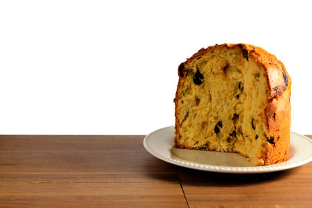 closeup panettone on ceramic plate on wooden table, white background, front view