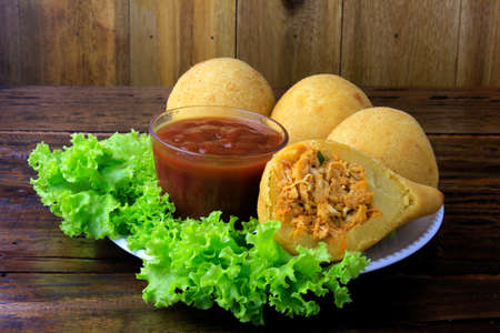 Coxinha in the dish, traditional Brazilian cuisine snacks stuffed with chicken, on rustic wooden table. Close up