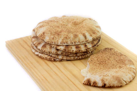 Pita bread isolated on white background in wooden spatula. Traditional and typical food of Arabic cuisine