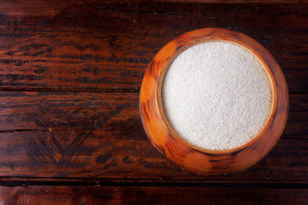 cassava flour (farinha de mandioca) in wooden bowl isolated on rustic table. food typical of brazilian cuisine Banque d'images