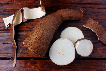 fresh cassava and peels and slices on rustic wooden table. Top view