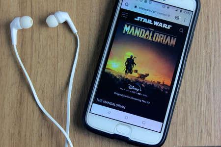 Rio de Janeiro, Brazil - November 28, 2019: The Mandalorian logo, Star Wars site on the mobile phone screen. It's a Disney Studios television series set in the Star Wars universe.