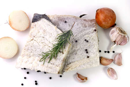 dry salted raw cod isolated over white background, accompanied by pepper, onion, garlic, parsley, spices. top view