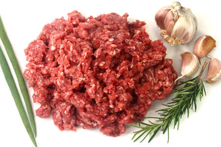 raw minced meat isolated on white background with green leaves and condiments. Top view Zdjęcie Seryjne