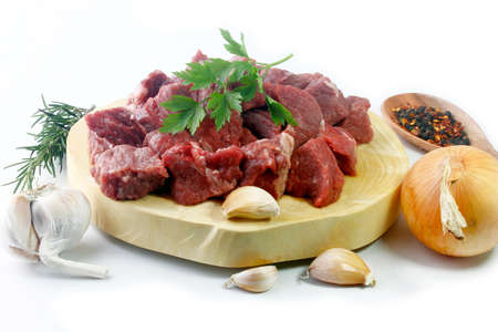 pile of cube chopped pile raw diced beef cubes with spices on wooden board isolated over white background. Top view Banque d'images