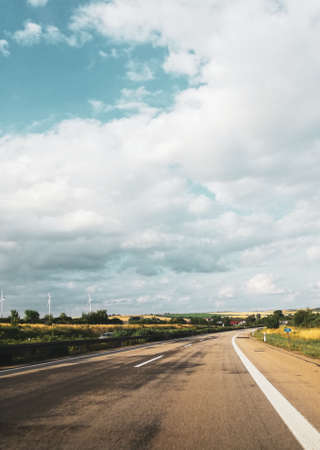 highway road in the countryside with bly sky and clouds