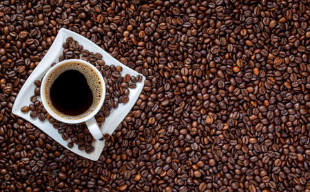 cup of coffee on roasted coffee beans background