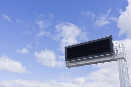 Electronic advertising panel against a background of blue sky with clouds