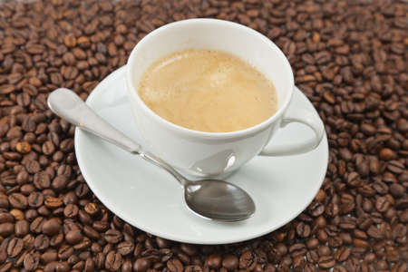 Cup of coffee sitting in a bed of coffee beans Stock Photo