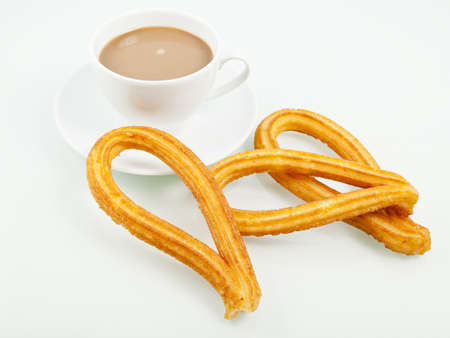 churros: Typical spanish churros with a cup of coffee. Churros is a sweet fried pastry for breakfast.
