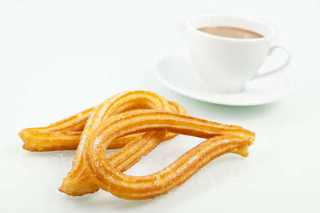 Typical spanish churros with a cup of coffee  Churros is a sweet fried pastry for breakfast