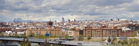 Madrid Skyline with mountains on background from Manzanares park.