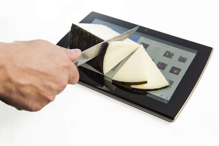 android tablet: Cutting cheese with a kitchen knife on an Android tablet isolated on white background Stock Photo