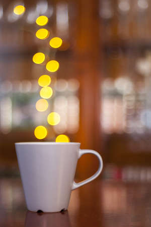 A mug of hot coffee or tea and with steam of lights  Natural bokeh