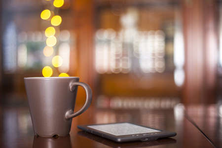 A mug of hot coffee or tea and with steam of lights and an e-reader device  Stock Photo