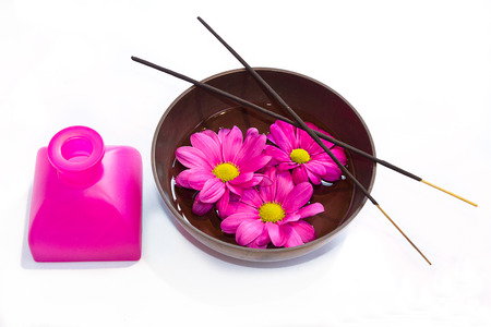 rin gong: A Tibetan bowl with massage oil, flowers and incense sticks and an oil bottle, isolated on white background  Stock Photo