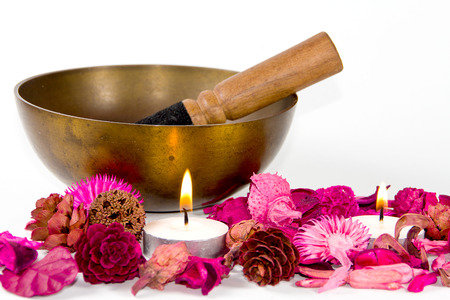 Studio shot of a tibetan bowl, some pink flowers and candles, over white background. photo