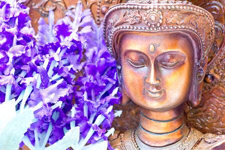 buena postura: Tiro del estudio de la cabeza de una estatua de bronce de Buda y flores de color p�rpura de la tela Foto de archivo