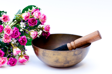 Studio shot of a Tibetan bowl with pink fabric roses, isolated on white background. photo