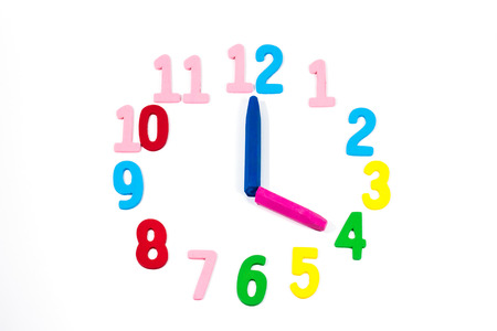 clockwise: Studio shot of a clock made with wood numbers and plastic pencils as clockwise, isolated on white background
