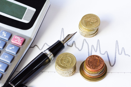 Studio shot of a fountain pen, calculator, stacks of coins and stock chart, on white background. photo
